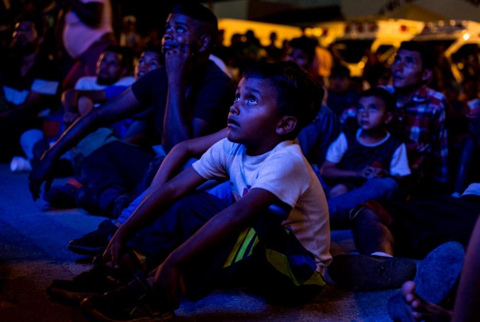 Un niño migrante mira un película en el albergue provisional en Sayula de Alemán, Veracruz.