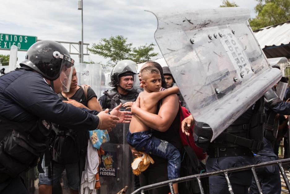 Viernes 19 de octubre. los migrantes forzaron el portón mexicano, pero no consiguieron sobrepasar al contingente de policías federales antimotines que los replegaron usando gas lacrimógeno. En la fotografía, policías mexicanos intentan calmar a un niño que viajaba con su madre (Fuente: Fred Ramos, El Faro).