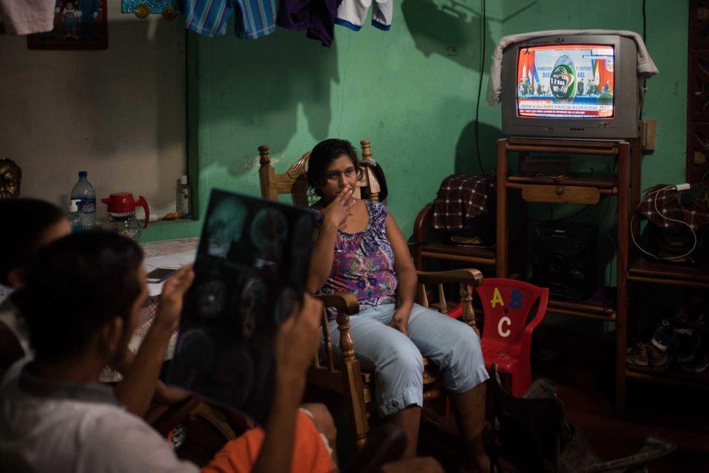 Juan Bosco Rivas Martínez se recupera del impacto de bala en su casa de habitación en Masaya. Mientras mira su radiografía con su madre al fondo (Fuente: confiencial.com.ni)