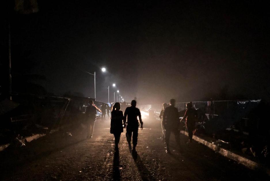Sábado 20 de octubre. Una pareja de migrantes hondureños camina sobre el puente fronterizo entre Guatemala y México, durante la noche. Con el paso del tiempo, un puente donde apenas cabían los cuerpos fue teniendo espacios libres, gracias a la decisión de cientos de pasar de forma irregular (Fuente: Fred Ramos, El Faro).