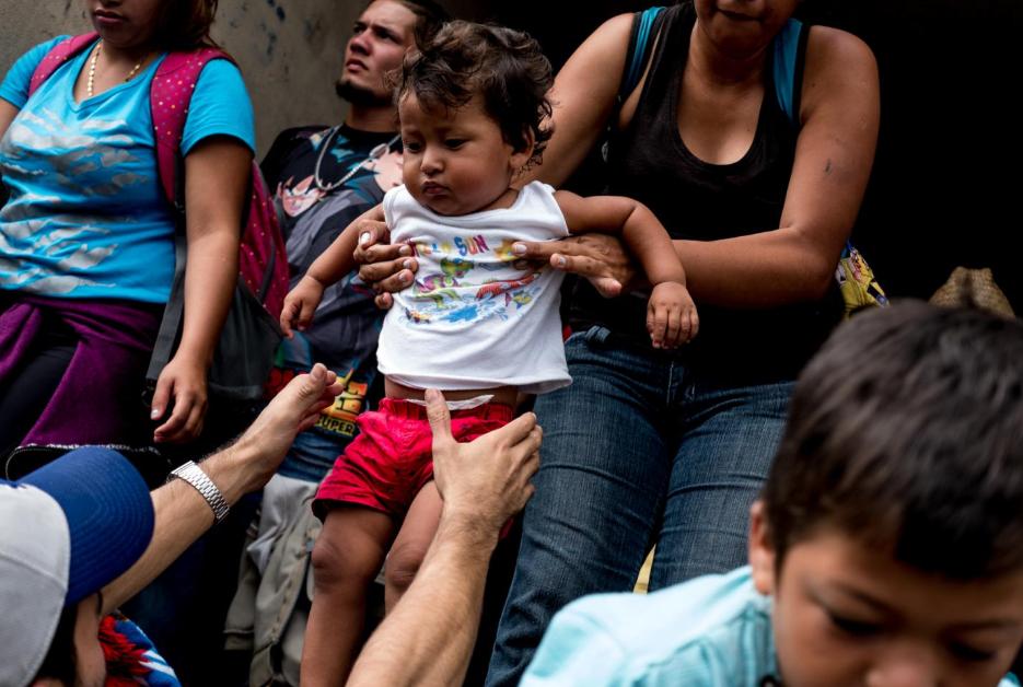 Migrantes centroamericanos ayudan a bajar a una niña de un camión que les dio aventón, en Isla, Veracruz, el 3 de noviembre. Cientos de niños viajaron en camiones desde Sayula de Alemán, Veracruz, a Puebla: un trayecto de 350 kilómetros.
