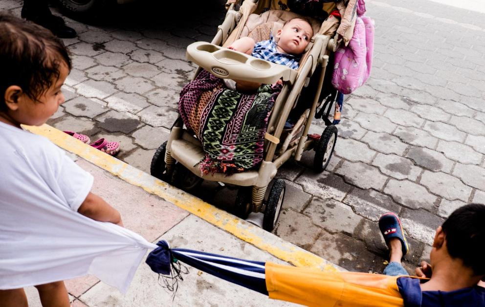 Heilie Mejía, de dos años, y Ángel Mejía, de 6, fueron amarrados entre sí por su madre, Olga Rodríguez, usando sus camisas. Rodríguez, hondureña, asegura que amarra a sus hijos cuando se ponen muy inquietos. Ella es una madre soltera que decidió unirse a la caravana con sus cuatro hijos. Los otros dos son un bebé de diez meses y una niña de cuatro años. Era vendedora ambulante, pero asegura que ese trabajo no le alcanza para mantener con dignidad a sus cuatro niños.