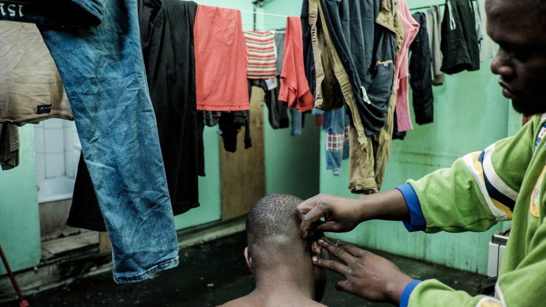 Un haitiano le corta el pelo a uno de sus coterráneos en el pasillo –que también hace de cocina- del segundo piso. Foto: Jorge Vargas | Migrar Photo