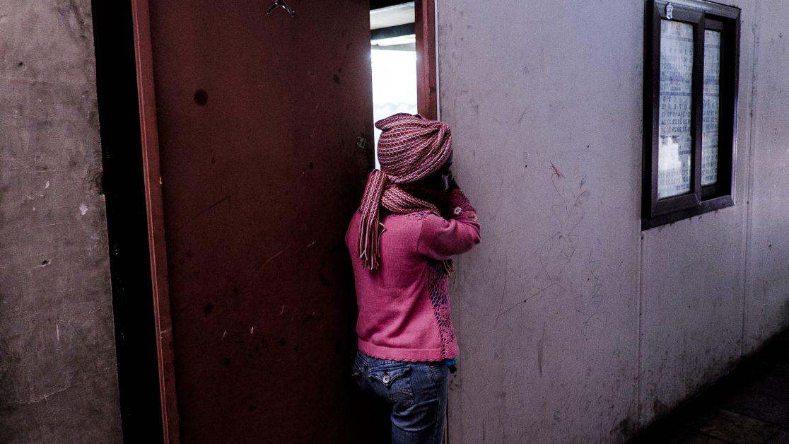 Una niña observa a sus vecinos limpiando, de forma colectiva, el aseo del pasillo. Foto: Jorge Vargas | Migrar Photo