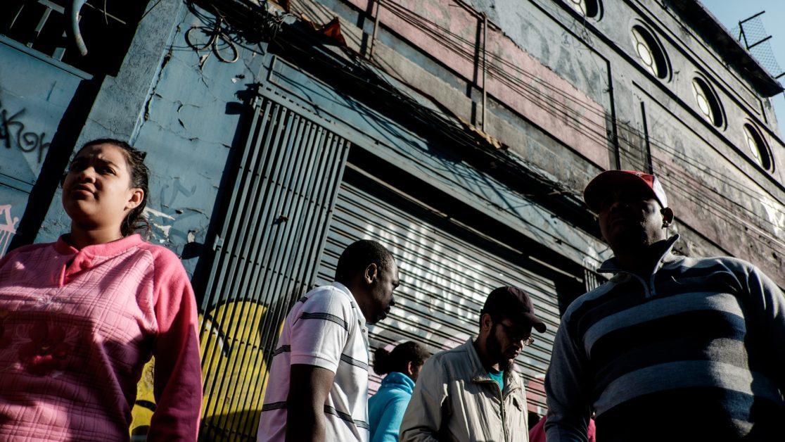 Los vecinos se organizan fuera del galpón luego de que uno de los habitantes se enfrentara duramente con el arrendador ante los constantes reclamos por las precarias condiciones en las que viven. Foto: Jorge Vargas | Migrar Photo