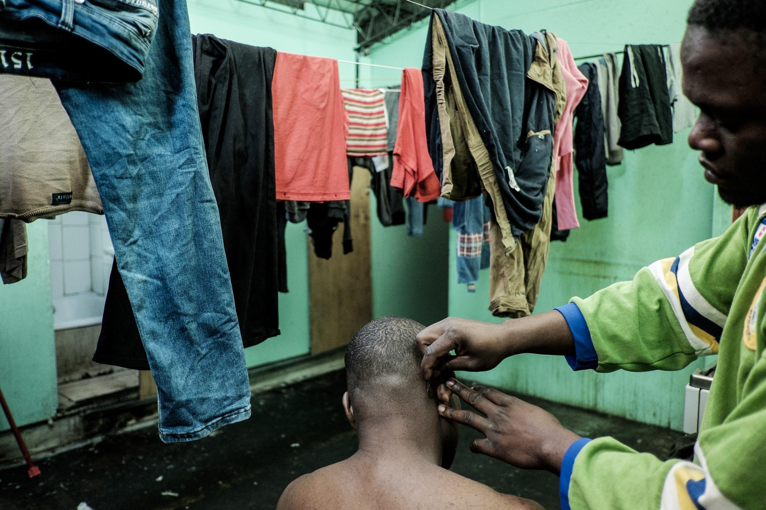 6.Un haitiano le corta el pelo a uno de sus coterráneos en el pasillo –que también hace de cocina- del segundo piso. Foto: Jorge Vargas | Migrar Photo