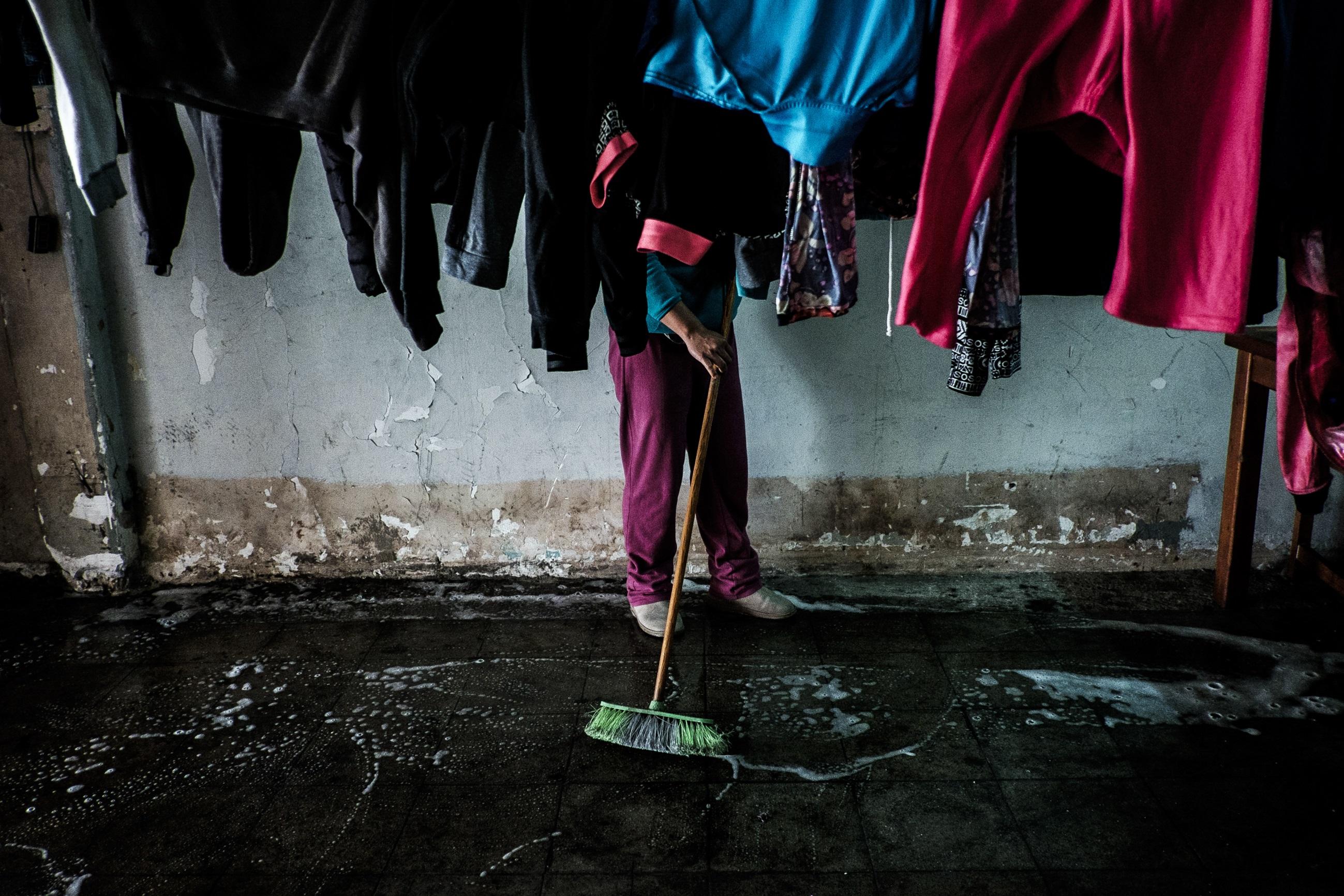 Una mujer escobilla el suelo entremedio de la ropa colgada en el primer piso. Foto: Jorge Vargas | Migrar Photo