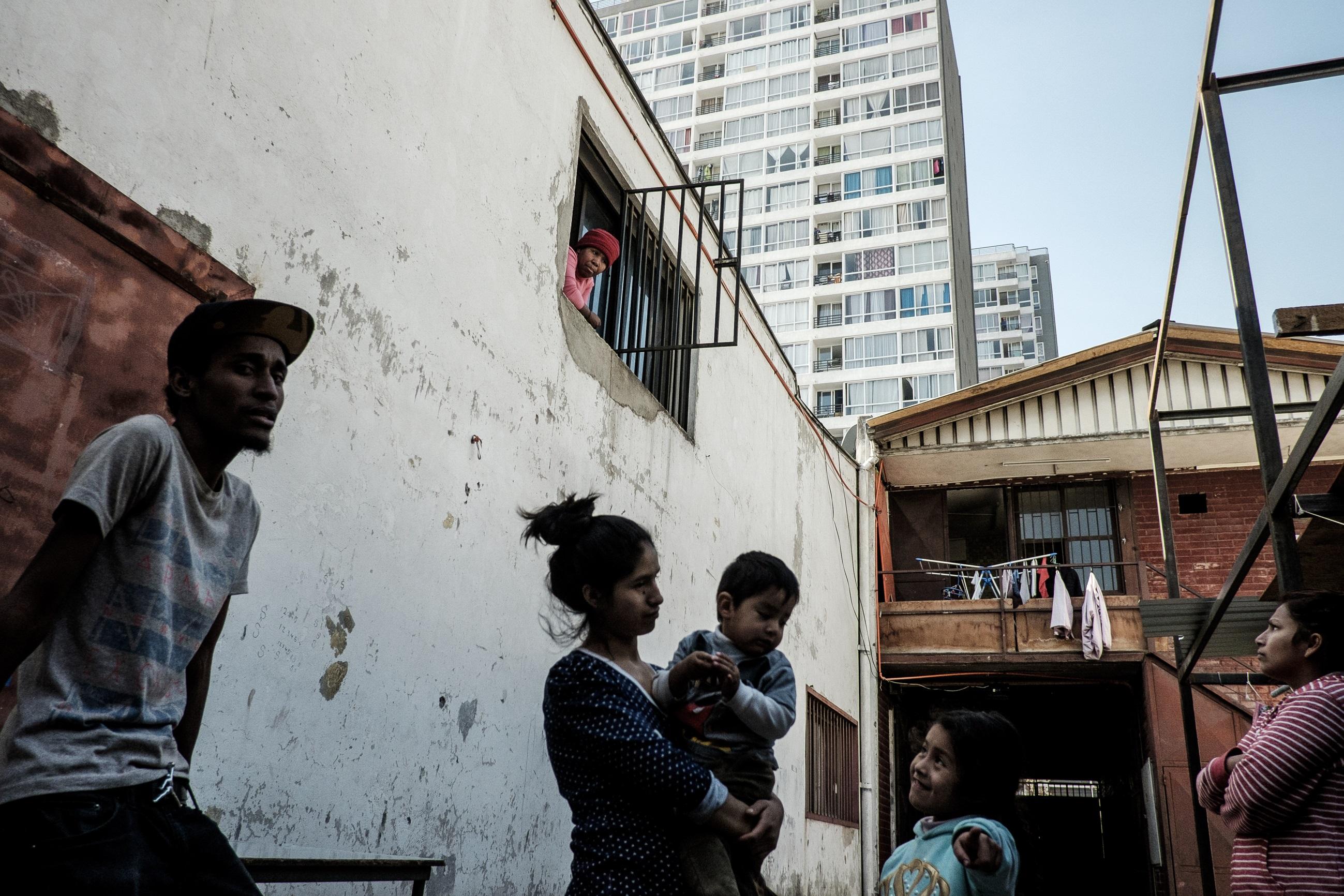 Un grupo de vecinos conversa sobre su actual situación luego de que su arrendador se fuera sin dejar indicios de su nuevo paradero. Foto: Jorge Vargas | Migrar Photo