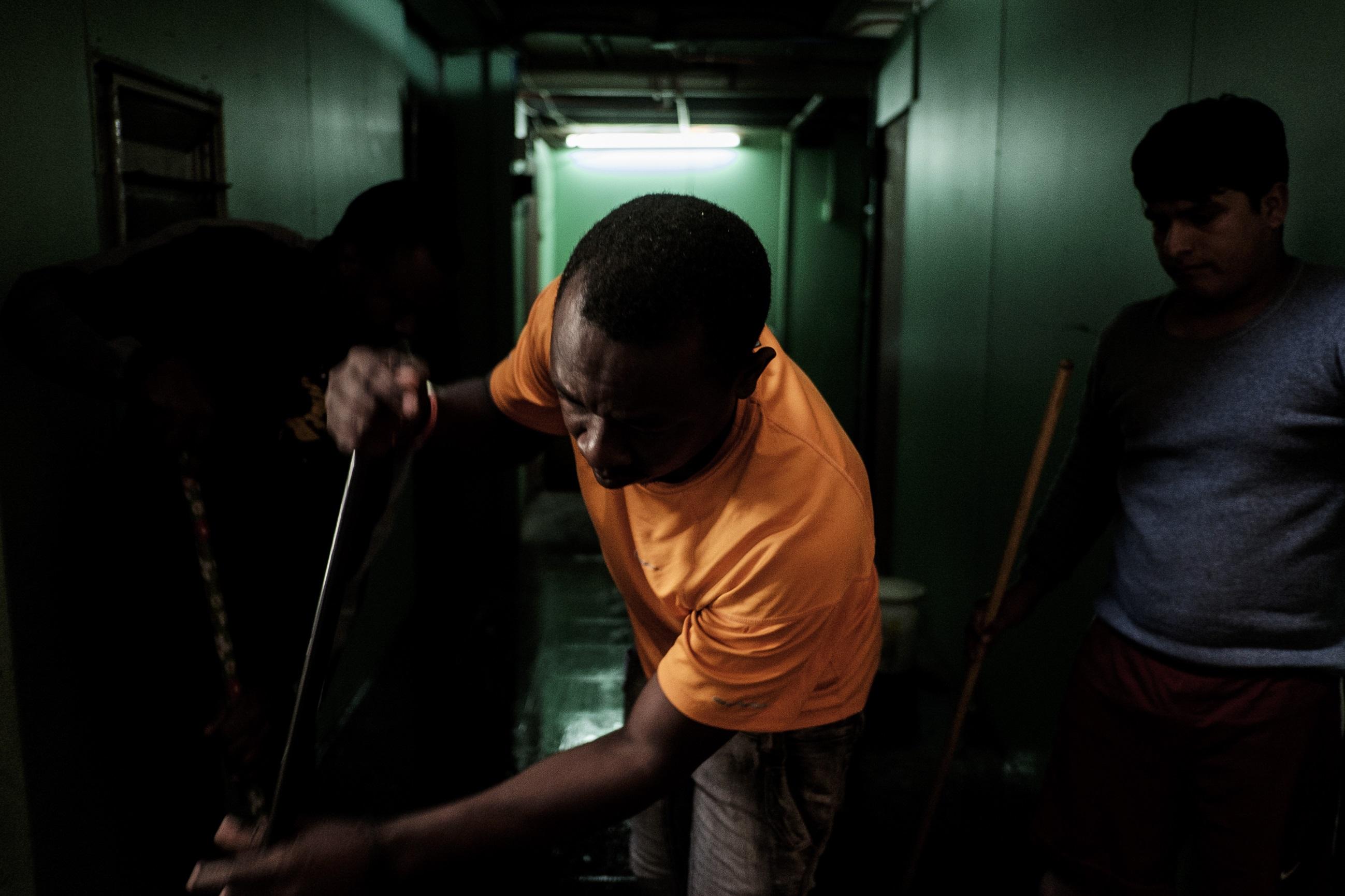 Tres hombres, de distintas nacionalidades, limpian el piso que conecta directamente con el segundo piso del galpón. Foto: Jorge Vargas | Migrar Photo