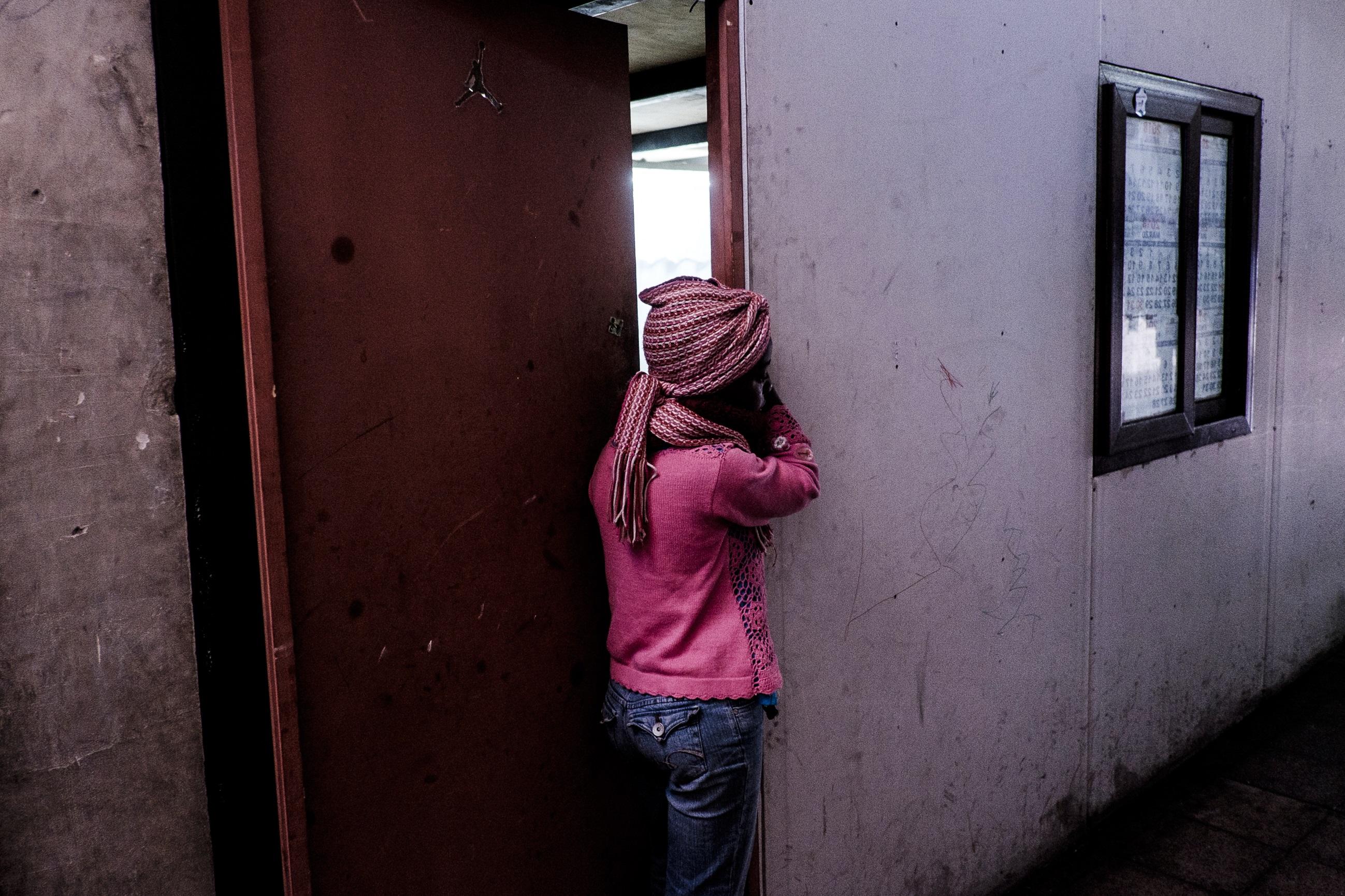 Una niña observa a sus vecinos limpiando, de forma colectiva, el pasillo. Foto: Jorge Vargas | Migrar Photo