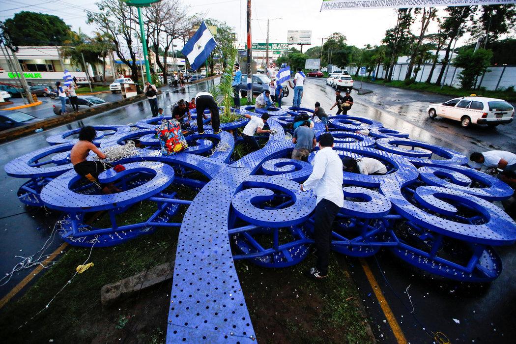 Manifestantes parados sobre la escultura de metal del árbol de la vida, derribada por los inconformes durante una protesta contra el gobierno del presidente Ortega en Managua, el 26 de mayo (Fuente: nytimes.com)