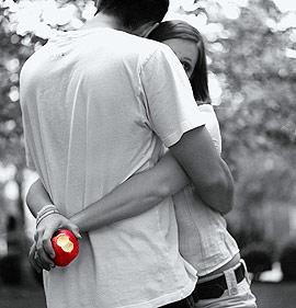 Pareja abrazada con manzana en la mano